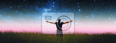 Obraz Man with arms wide open standing on the grass field against the night starry sky. Elements of this image furnished by NASA.