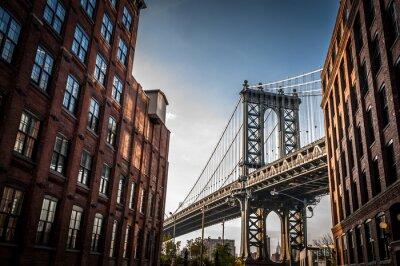 Obraz Manhattan Bridge vidět z úzké uličky ohraničená dvěma cihlovými budovami za slunečného dne v létě