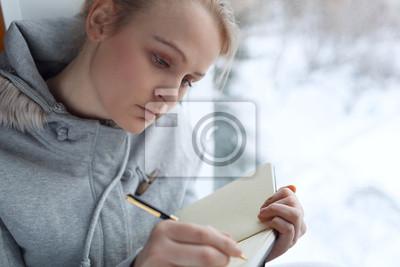 Mladá dívka psaní v jejím deníku.