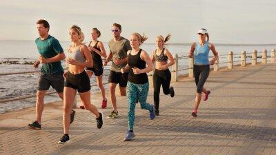 Obraz Mladí lidé běží podél pláže promenády