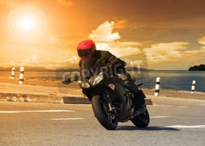 Obraz Mladý muž na koni velký kolo motocyklu proti ostré zatáčce asfaltové silnici dálnic s venkovské použití jezero scéně mužských sportovních aktivit a motorsportu hobby na dovolenou dovolenou