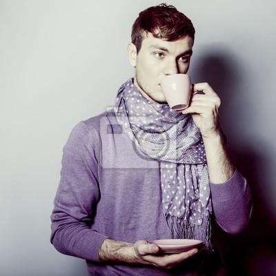 Mladý muž s šálkem kávy v ruce