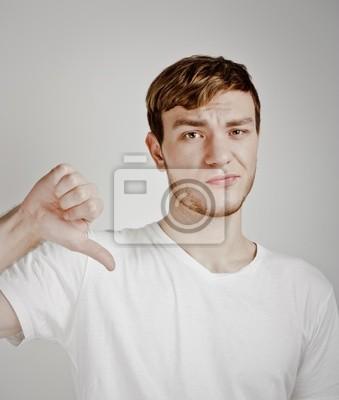 Mladý muž ukazuje palec dolů