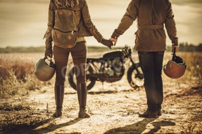 Obraz Mladý, stylový kavárna závodník pár na vintage zakázkové motocykly v poli.