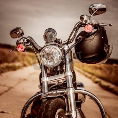Obraz Motocykl na silnici s přilbou na řídítkách.