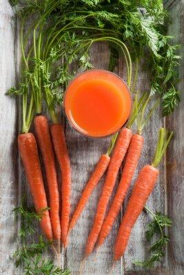 Obraz Mrkev a mrkev šťáva. Zdravé jídlo - mrkev a mrkev šťávu na dřevěném pozadí