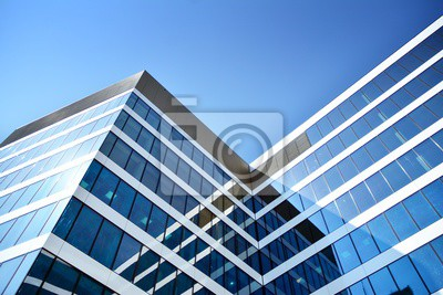 Obraz New office building in business center. Wall made of steel and glass with blue sky.