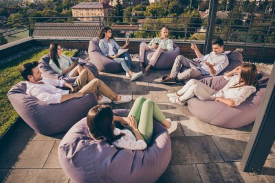 Obraz Nice attractive stylish partners leaders company unity sitting in bag chairs discussing project development on roof outside outdoor sunny day
