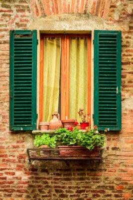Okna ve starém domě zdobené květináče a květiny