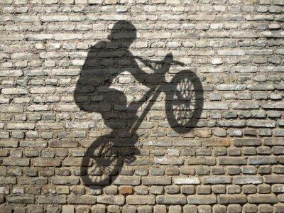 ombre de d'homme en BMX sur mur de briques