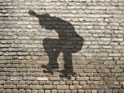 ombre de skate strávník sur mur de briques