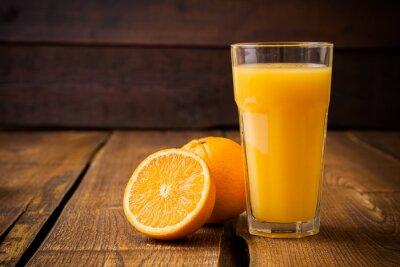 Obraz Oranžové ovoce a sklenice džusu na hnědé dřevěné pozadí