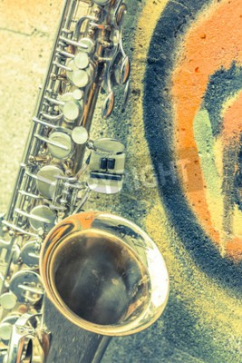 Obraz Osamělý starý saxofon opře cihlové zdi mimo opuštěné jazzovém klubu