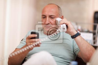 Podnikatel v kanceláři, mluví na dvou telefonech