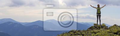Obraz Pohled zezadu na mladé štíhlé backpacker turistická dívka se zdvižené paže stojící na skalnatém vrcholu proti jasně modré ranní obloze se těší mlhavé horské panorama. Cestovní ruch, cestování a horole