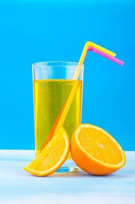 Obraz pomerančový džus ve sklenici s barevnými stébla a plátky pomeranče na modrém pozadí