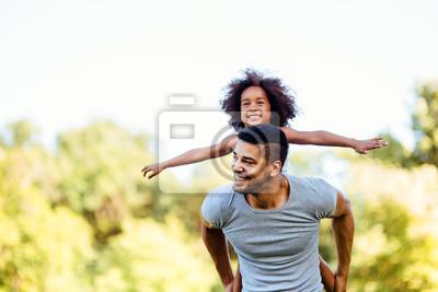 Obraz Portrét mladého otce nesoucí jeho dceru na zádech