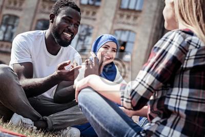 Obraz Příjemná konverzace. Potěšený pěkný pozitivní člověk se usmíval a ukázal na svého přítele, když měl příjemný rozhovor