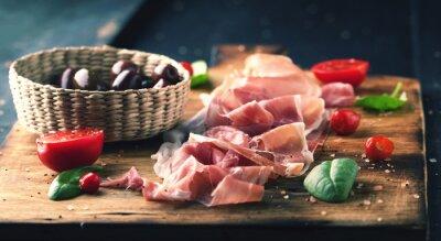 Obraz Prosciutto s chlebem na dřevěné desce s olivami