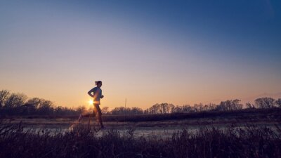 Obraz ragazza Atletica si allena All'Aperto su terra di sera