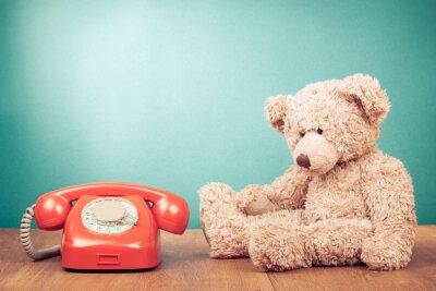 Obraz Retro červený telefon a medvídek v blízkosti mátově zelená zeď