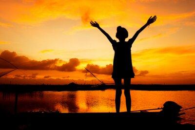 Obraz roztomilá holčička hrát na řece západu slunce na pozadí