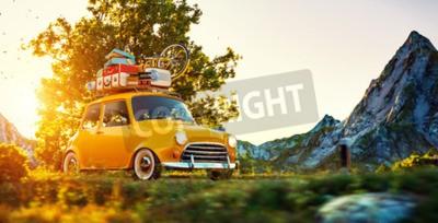 Obraz Roztomilé malé auto s kufry a na horním kole jde nádhernou silnicí při západu slunce