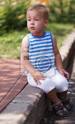 Roztomilý chlapec seděl na obrubníku