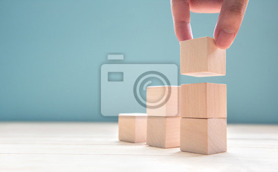 Obraz Ruční uspořádání dřevěné kostky stohování jako krok schodiště. Obchodní koncept růst úspěch proces na modrém pozadí, kopie prostor.