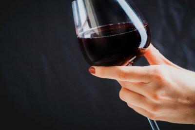 Obraz Ruka držící sklenku červeného vína na tmavě šedém pozadí