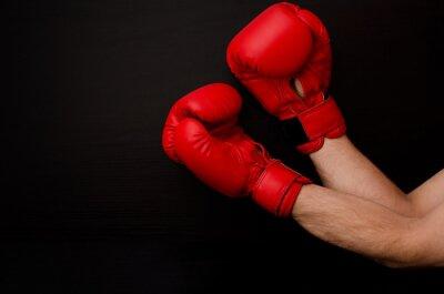 Obraz Ruku v červených boxerské rukavice na rohu rámečku na černém pozadí, prázdný prostor