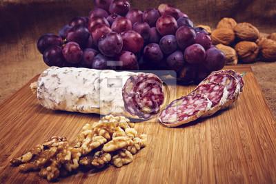 Obraz salám s ořechy na prkénku s hroznovým vínem