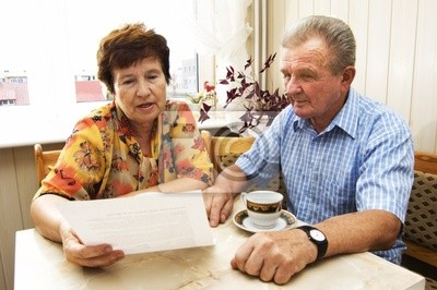 Senior pár studuje dokument spolu v domě