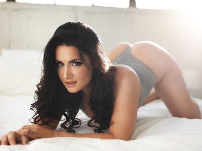 Obraz sexy model na jasně osvětlené posteli v erotickém představovat