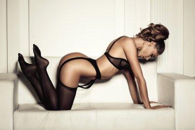 Obraz sexy žena v černém prádle svůdná sedí na gauči v STO