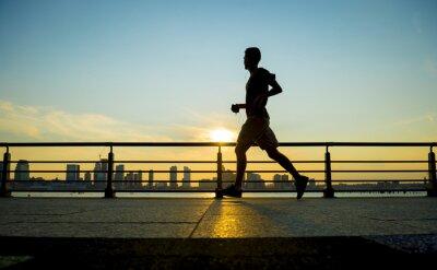 Obraz Silueta běžců běží při západu slunce v přední části městského panoramatu