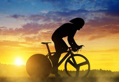Obraz Silueta cyklista na silnici závodní kolo při západu slunce.