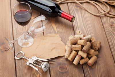 Obraz Sklenka červeného vína, láhev a vývrtka na rustikální dřevěný stůl