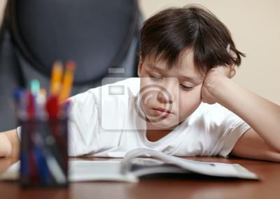 Školní chlapec studuje tvrdě na své knize doma.