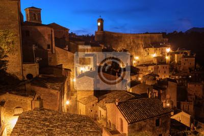 Sorano - tuf město v Toskánsku. Itálie. Pohled do soumraku s osvětlením, cestovní pozadí