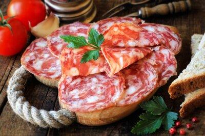 Obraz Španělské tapas - nakrájený salame na rustikální dřevěném prkénku s chlebem a rajčaty