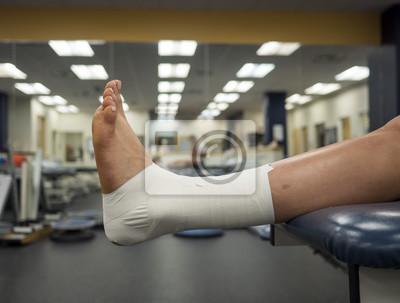 Obraz Sportovní noha s páskovou páskou pro podporu visící ze stolu na lékařské klinice