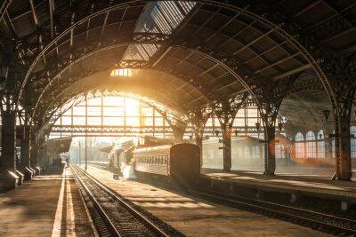 Obraz Staré nádraží s vlakem a lokomotivou na nástupišti čeká na odjezd. Večerní sluneční paprsky v kouřových obloucích.
