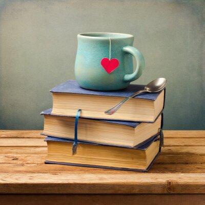 Obraz Staré vintage knihy a šálek s tvaru srdce na dřevěném stole