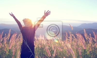 Obraz Šťastná žena se těší přírodě na trávě louku na vrcholu horské útesu se sluncem venku. Svoboda koncepce.