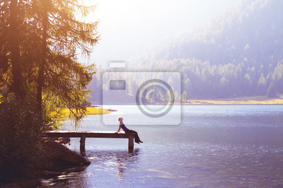 Obraz Šťastná žena sedí na molu a usmívá se, štěstí nebo inspirace koncept, užít si života