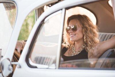 Obraz Šťastný, bezstarostné žena těšit na retro auto, horký letní den.