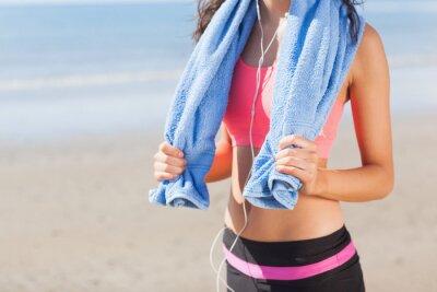 Obraz Střední část zdravé ženy s ručníkem kolem krku na pláži