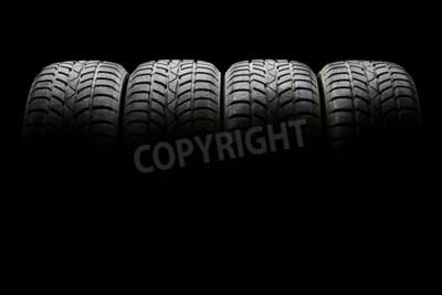 Obraz Studio shot ze sady čtyř černých automobilů pneumatik seřazených horizontálně v temném prostředí na černém pozadí