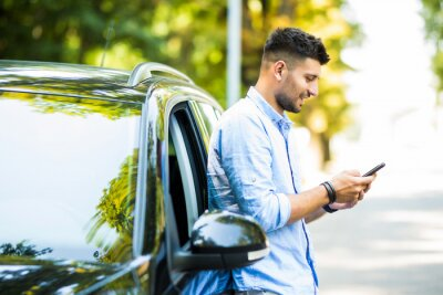 Obraz Successful young man standing by his car texting on mobile phone